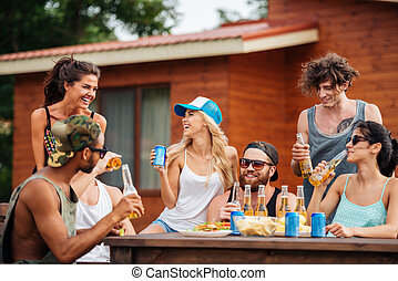 Group of cheerful young people drinking beer and laughing outdoors