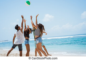 Group of cheerful young people playing with volley ball
