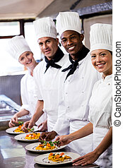 Group of chefs holding plate of prepared pasta in kitchen