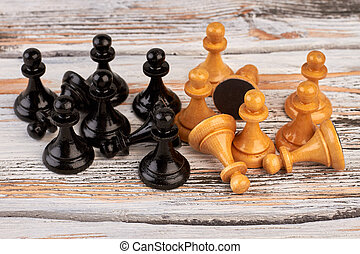 Group of chess pawns on wooden background.