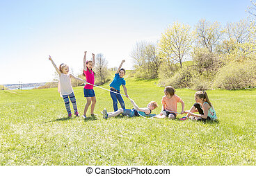 Group of child have fun on a field with rope