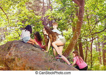 Group of children climb on the rock in forest