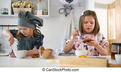 Group of children decorating cookies with jam, close up