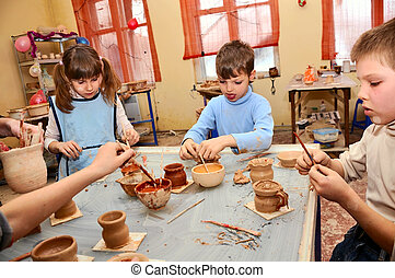 group of children decorating their clay pottery - young...