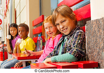 Group of children diversity sit outside in cafe