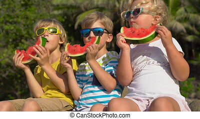 Group of children eating watermelon sitting on a tropical beach. Childhood concept. Summer concept