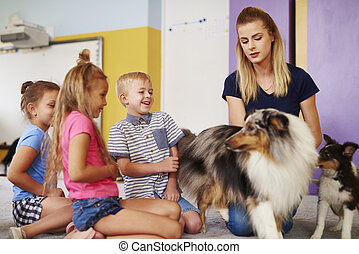 Group of children having fun with dog during therapy