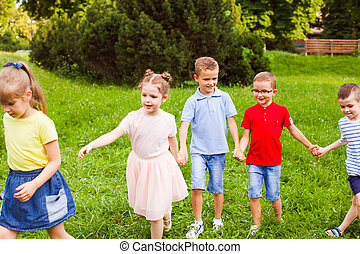 Group of children holding hands and playing outdoors game