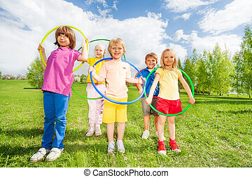 Group of children holding hula hoops in park