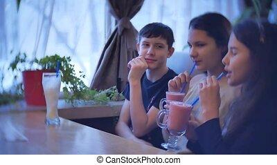 group of children in a cafe drink milkshake. teenagers...