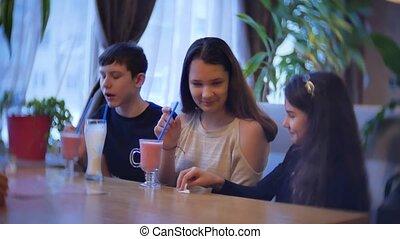 group of children in a cafe drink milkshake. teenagers indoors kids children in cafes slow motion video fun indoors joy communication