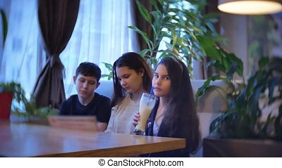 group of children in a cafe fast food are eating milkshakes. teenagers kids children in cafes slow motion video fun joy communication indoors