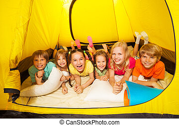 Group of children laying in a tent