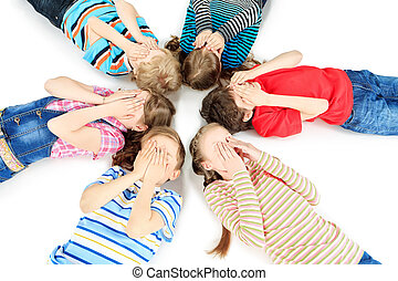 covering their faces - Group of children lying on a floor ...