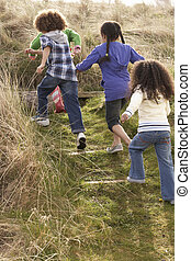 Group Of Children Playing In Field Together