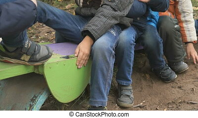 Group of children riding on seesaw sitting together