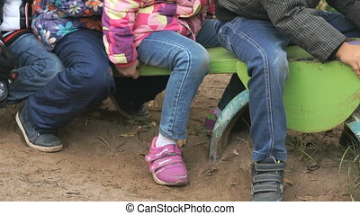 Group of children riding on swing sitting together