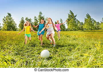 Group of children running to the ball in meadow