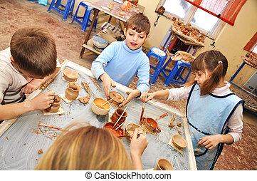 group of children shaping clay in pottery studio - group of...