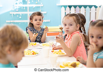 Group of children sitting at the table with lunch and eat appetizing. Kids have a dinner in kindergarten