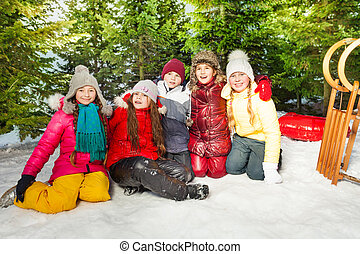 Group of children sitting on snow in winter time