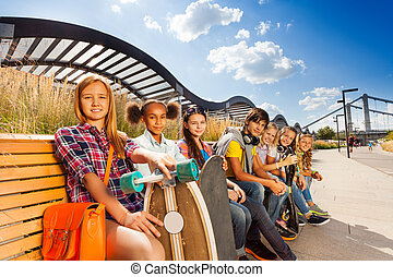 Group of children sitting on wooden bench together