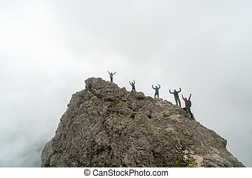 group of climbers standing on a jagged mountain peak and waving their hands in the air