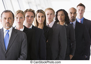 Group of co-workers standing in office space smiling (high...