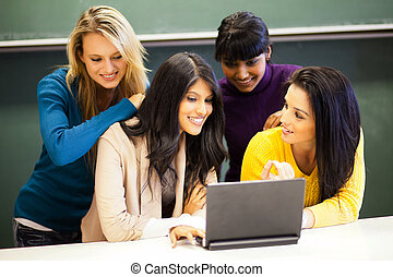 college students discussing project on laptop in classroom -...