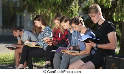 Group of college students studying together - Side view of...