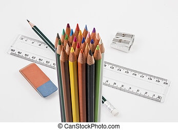 Group of colored pencils with basic school supplies on a white background