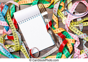 Group of colorful measure tapes, open notebook and fork on wooden background with empty space for your idea. Top view of healthy lifestyle concept