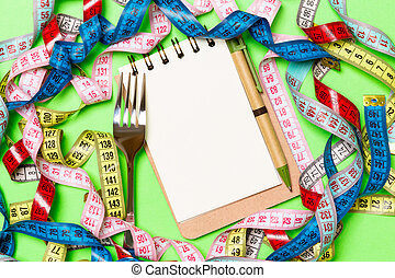 Group of colorful measure tapes, pen, open notebook and fork on green background with empty space for your idea. Top view of healthy lifestyle concept