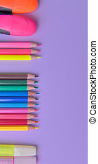 group of colorful pencils and pens arranged on the left and a copy space on the right on mauve background