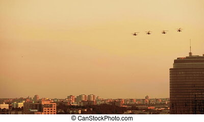 Group of combat helicopters over the city K-52, red warm...