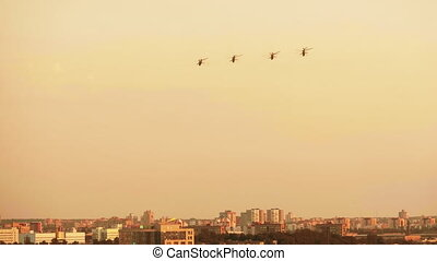Group of combat helicopters over the city - red warm sunset