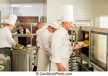 Group of cooks in professional kitchen prepare meals ...