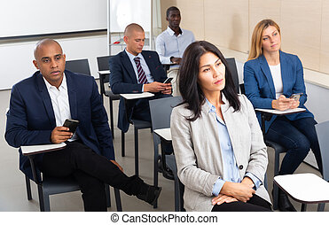 Group of corporate employees listening to business training