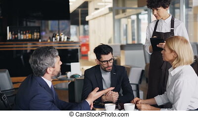 Group of coworkers talking to waitress in cafe making order during lunch break
