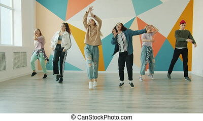 Group of creative young people dancing in modern studio jumping gesturing
