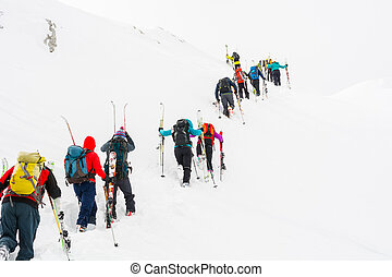 Group of cross-country skiers ascending a steep slope.