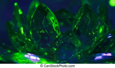Group of crystals rotate around its axis on highlighted with green laser