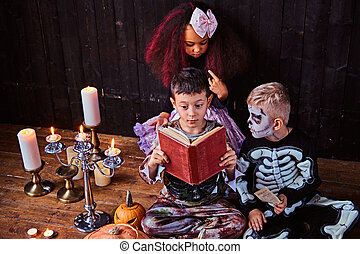 Group of cute multiracial kids in scary costumes reading horror stories in an old house, during Halloween party.