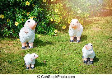 Group of cute white sheep statue made of clay on grass in the garden park