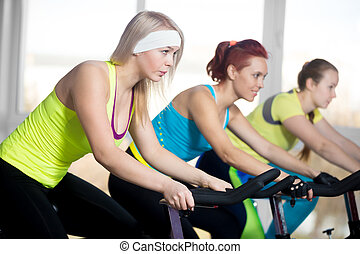 Group of cyclist women in fitness center