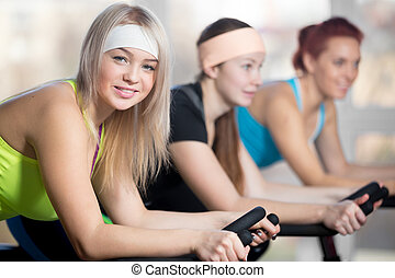 Group of cyclist women in gym