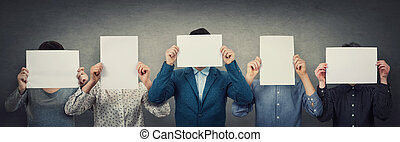 Group of different people, business team, each covering his face using a blank white paper. Teamwork thinking and cooperation process. Persons hiding identity behind an empty sheet, anonymous concept.