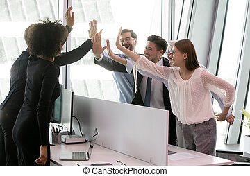 Group of diverse coworkers giving high five share common success
