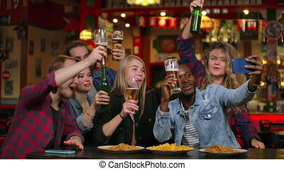 Group of diverse friends taking selfie on mobile phone in bar