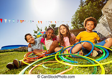 Group of diverse kids sit with hula color rings